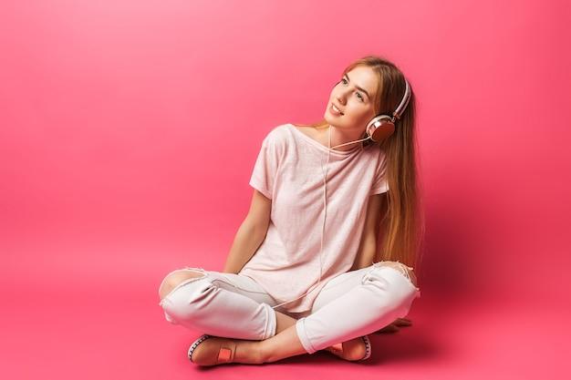 Portret van vrolijke mooi meisje zittend op de vloer en wegkijken, luisteren naar muziek in de koptelefoon