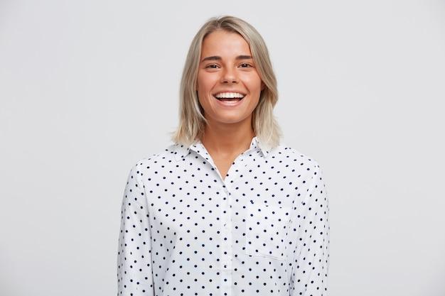Portret van vrolijke mooie blonde jonge vrouw draagt polka dot shirt voelt zich gelukkig, staand en glimlachend geïsoleerd over witte muur