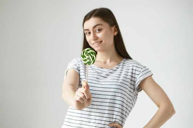Portret van vrolijke mooie brunette jonge vrouw in gestreepte casual t-shirt met lolly, glimlachend met positieve vrolijke gezichtsuitdrukking. selectieve aandacht voor hard snoep