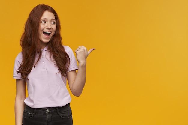 Portret van vrolijke, mooie dame met lang gemberhaar. roze t-shirt dragen. emotie concept. wijzend met de duim en naar rechts kijken naar kopie ruimte, geïsoleerd over oranje muur