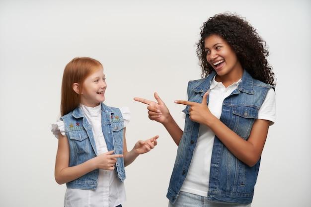 Portret van vrolijke mooie dames in vrijetijdskleding die met opgeheven handen op elkaar tonen en vreugdevol glimlachen, goede tijd samen hebben terwijl poseren op wit