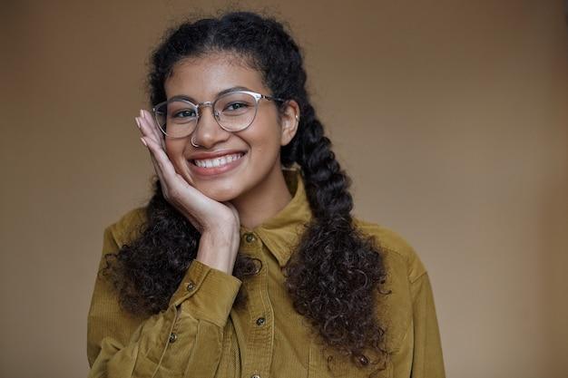 Portret van vrolijke mooie jonge donkere vrouw die haar krullend bruin haar gevlochten houdt, gelukkig kijkt met een brede glimlach en leunende kin op opgeheven hand, geïsoleerd