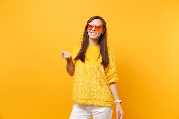 Portret van vrolijke mooie jonge vrouw in bont trui, witte broek, hart oranje bril staande geïsoleerd op felgele achtergrond. mensen oprechte emoties, lifestyle concept. reclame gebied.