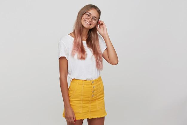 Portret van vrolijke mooie jonge vrouw met lang geverfd pastelroze haar draagt t-shirt, gele rok en bril staan, voelt zich gelukkig en poseren geïsoleerd over witte muur