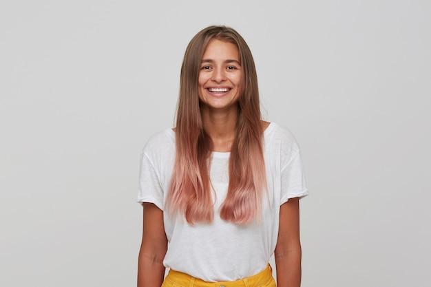 Portret van vrolijke mooie jonge vrouw met lang geverfd pastelroze haar voelt gelukkig en glimlachend geïsoleerd over witte muur