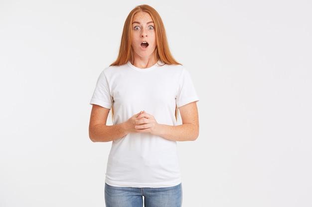 Portret van vrolijke mooie roodharige jonge vrouw met lang haar en sproeten draagt t-shirt