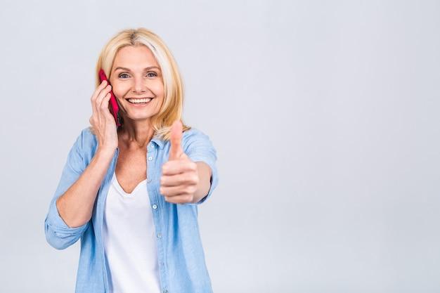 Portret van vrolijke mooie volwassen senior zakelijke blonde vrouw met behulp van mobiele telefoon. glimlachend, geïsoleerd over witte grijze achtergrond. duim omhoog teken.