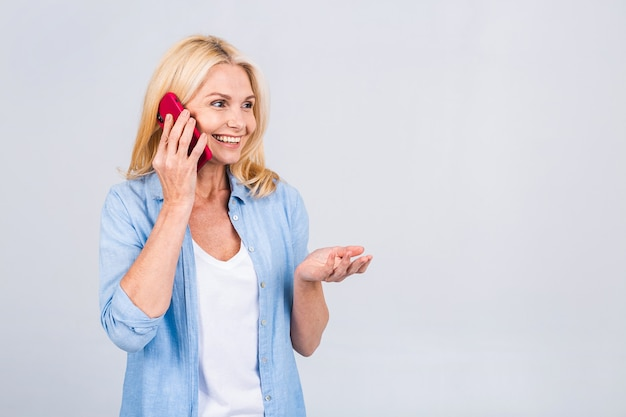 Portret van vrolijke mooie volwassen senior zakelijke blonde vrouw met behulp van mobiele telefoon. glimlachend, geïsoleerd over witte grijze achtergrond.