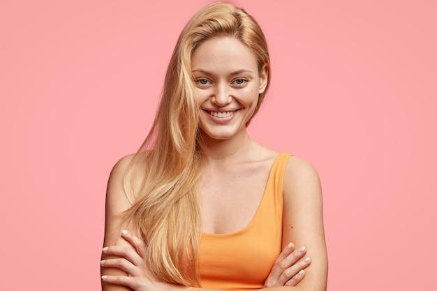 Portret van vrolijke mooie vrouw met gezonde huid, prettige vriendelijke glimlach, licht haar, houdt armen over elkaar, gekleed in oranje t-shirt