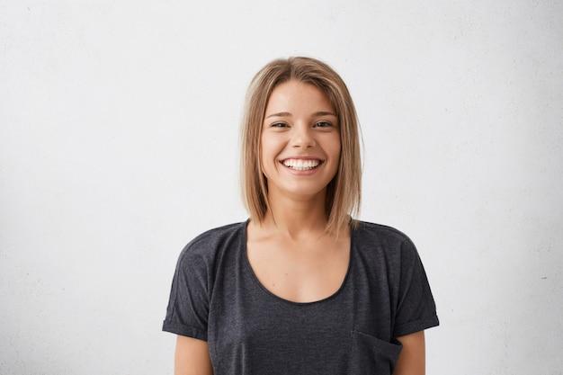 Portret van vrolijke mooie vrouw met trendy kapsel met donkere charmante ogen en boeiende glimlach. mensen, geluk, emoties en levensstijlconcept