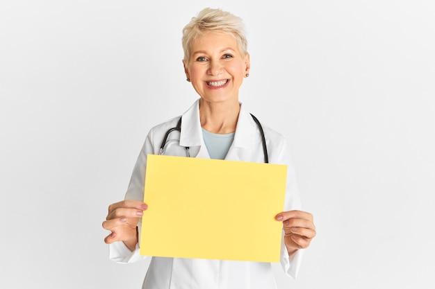 Portret van vrolijke mooie vrouwelijke arts of verpleegster van middelbare leeftijd die medische witte laag dragen die leeg leeg tekenraad met exemplaarruimte amera tonen