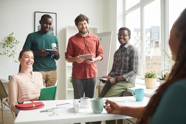 Portret van vrolijke multi-etnische team in gesprek met baas of manager tijdens zakelijke bijeenkomst in kantoor