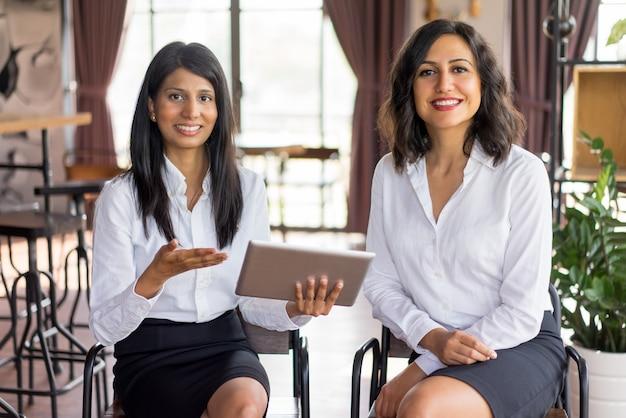 Portret van vrolijke multi-etnische vrouwelijke collega's die in zitkamerruimte samenkomen.
