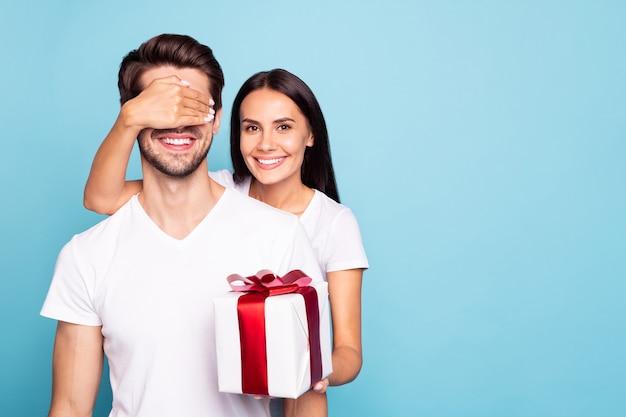 Portret van vrolijke ogen van het paarmeisje het sluiten van de kerel voorbereid geïsoleerde verjaardagsgift