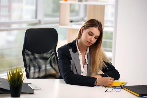 Portret van vrolijke onderneemster die op contractzitting aan bureau in bureau schrijft