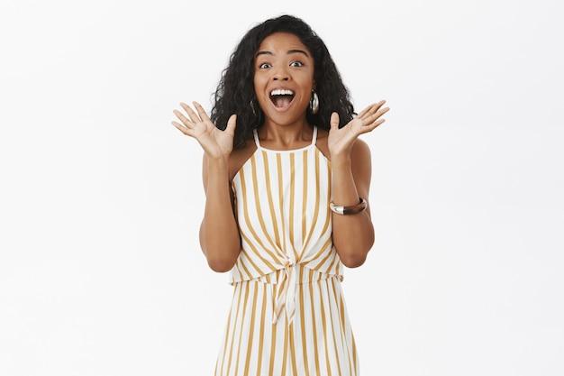 Portret van vrolijke opgewonden donkere vrouw die geweldig nieuws vertelt, opgeheven palmen van vreugde schudden
