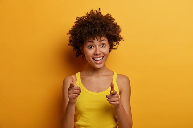 Portret van vrolijke opgewonden jonge african american vrouw wijst wijsvingers