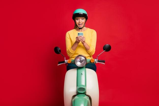 Portret van vrolijke opgewonden meisjeszitting op bromfiets die telefoon open mond gebruiken