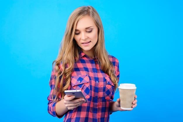 Portret van vrolijke opgewonden vreugdevolle vreugde leuke mooie mooie schattige mooie manager zakenvrouw dame sms'en met smartphone genieten van verse thee geïsoleerd op heldere blauwe achtergrond kopie-ruimte