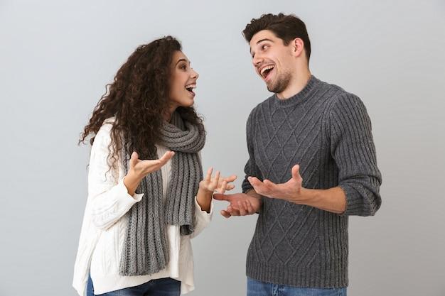 Portret van vrolijke paarman en vrouw die en met elkaar glimlachen praten, geïsoleerd over grijze muur