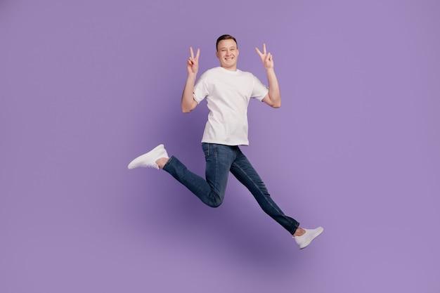 Portret van vrolijke positieve grappige kerel jump run maken v-tekens op paarse achtergrond