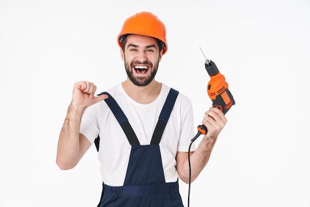 Portret van vrolijke positieve jonge man bouwer in helm poseren geïsoleerd over witte muur met boor wijzend naar zichzelf.