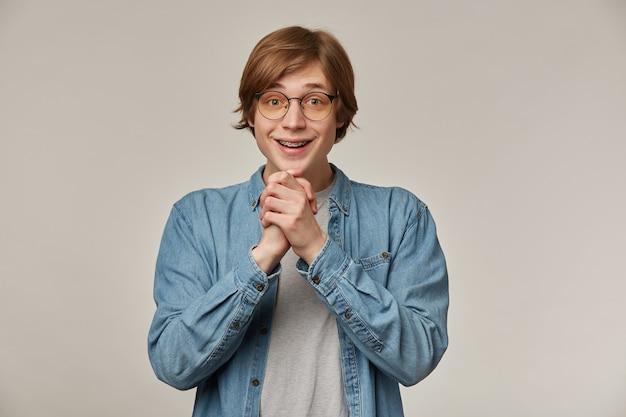 Portret van vrolijke, positieve man met blond haar. draagt een spijkerblouse, een bril en heeft bretels. houdt zijn handpalmen bij elkaar en glimlacht.