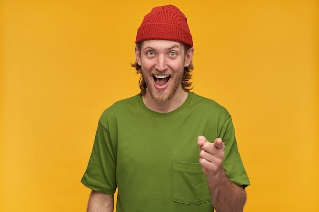 Portret van vrolijke, positieve man met blond kapsel en baard. het dragen van een groen t-shirt en een rode muts. lachend en wijsvinger naar je. geïsoleerd over gele muur