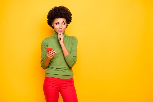 Portret van vrolijke positieve schattige mooie mooie charmante vrouw opzoeken in lege ruimte in rode broek met telefoon denken over herposten.