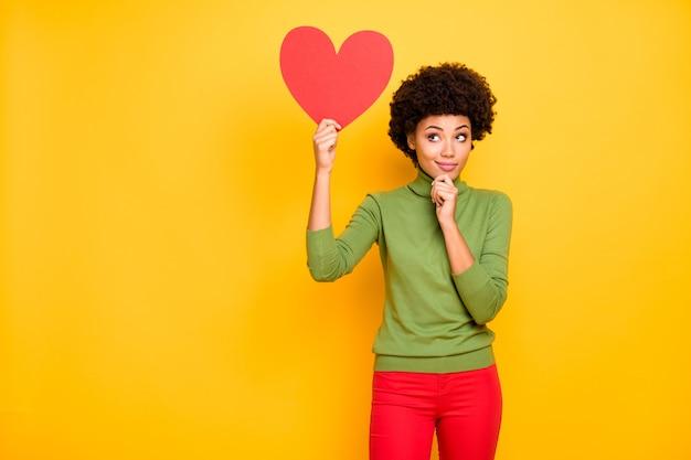 Portret van vrolijke positieve schattige vrij lieve vrouw die omhoog kijkt naar de hartvorm en denkt aan wie ze het cadeau moet doen.