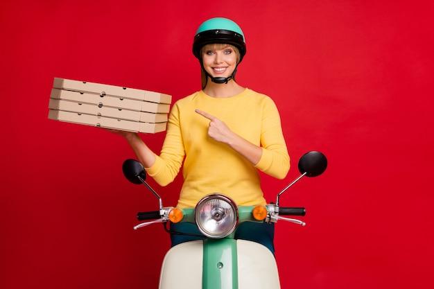 Portret van vrolijke promotor meisje zittend op bromfiets stapel stapel pizzadozen demonstreren