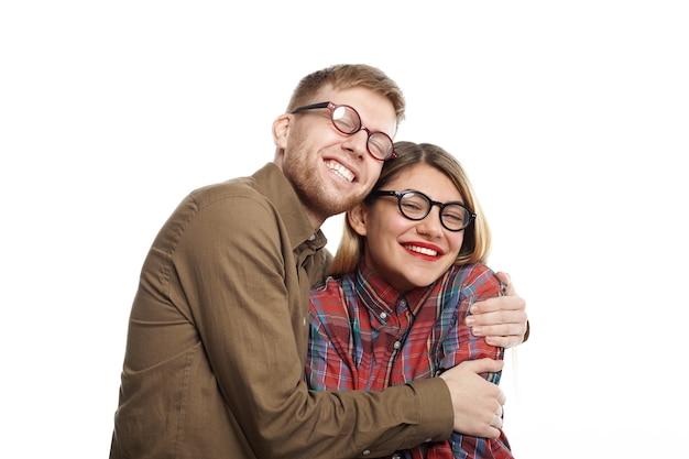Portret van vrolijke schattige jonge europese vriendin en vriend dragen soortgelijke stijlvolle ovale bril knuffelen, hun brede glimlach uiting van geluk en vreugde. zo blij om samen te zijn
