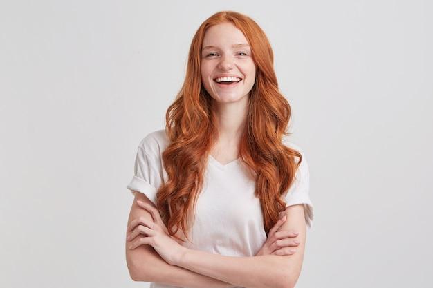 Portret van vrolijke schattige roodharige jonge vrouw met lang golvend haar