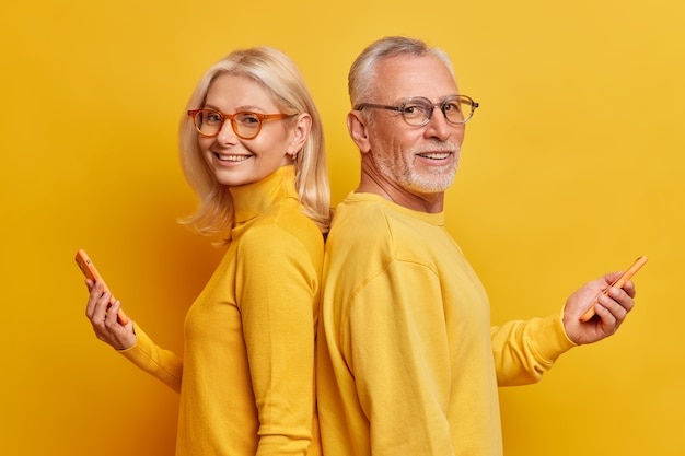 Portret van vrolijke senior vrouw en man staan in profiel met moderne gadgets houden smartphone hebben technologie verslaving dragen vrijetijdskleding geïsoleerd over gele muur