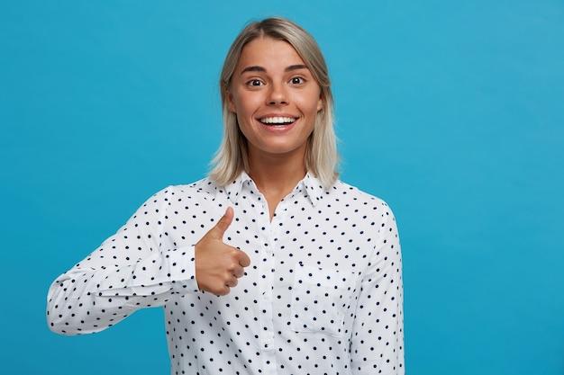 Portret van vrolijke speelse blonde jonge vrouw draagt polka dot shirt knipogen, flirten en plezier hebben geïsoleerd over blauwe muur