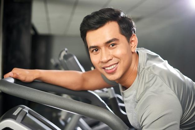 Portret van vrolijke sportieve man in de sportschool