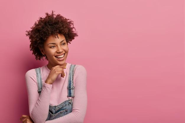 Portret van vrolijke tedere jonge vrouw met krullend afro haar lacht zachtjes en kijkt peinzend opzij, heeft charmante uitdrukking, denkt na over aangenaam moment in het leven, geïsoleerd op roze muur