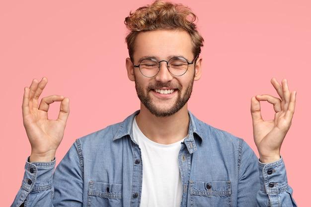Portret van vrolijke tevreden man met stoppels, staat in mudra-teken, houdt de ogen dicht, heeft een positieve glimlach, staat binnen tegen roze muur, draagt een spijkerbroek. mensen en lichaamstaal concept