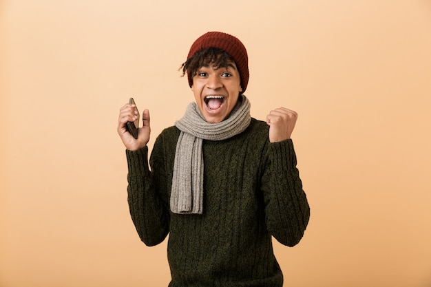 Portret van vrolijke tienerkerel die en hoed en sjaal draagt die en smartphone schreeuwen gebruikt, dat over gele muur wordt geïsoleerd