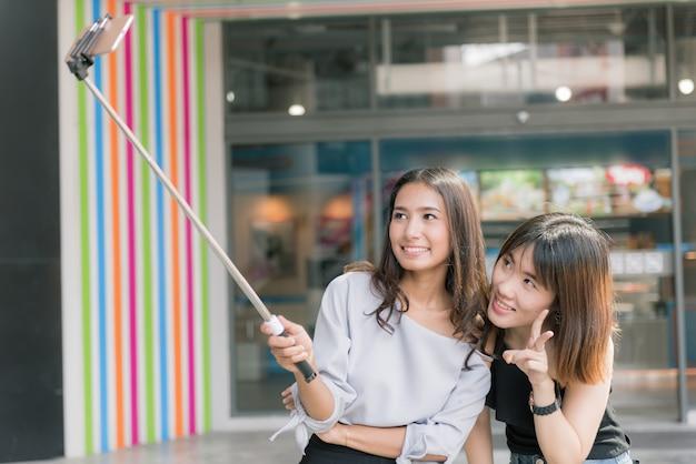 Portret van vrolijke twee glimlachende vriendinnen die een selfie maken bij winkelcomplex.