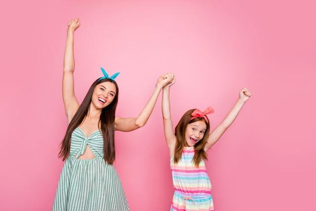 Portret van vrolijke twee vrouwen die handen houden die de rok van de hoofdbandenkleding dragen die over roze achtergrond wordt geïsoleerd