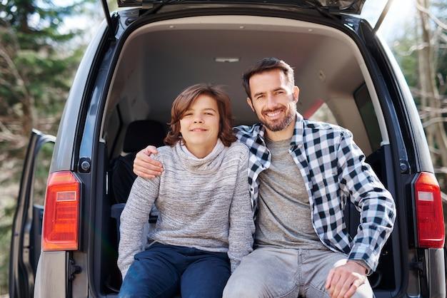 Portret van vrolijke vader en zijn tienerzoon omarmen