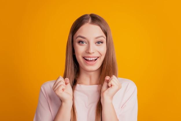 Portret van vrolijke verbaasde winnaar dame viert overwinning op gele achtergrond