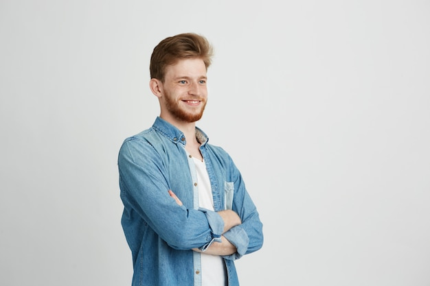 Portret van vrolijke vertrouwen jonge knappe man met baard glimlachen. gekruiste armen.