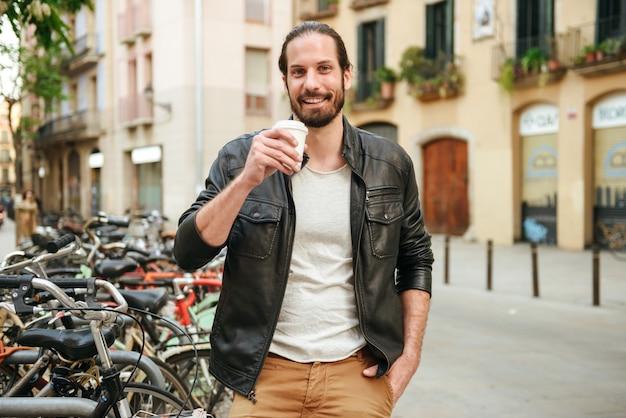 Portret van vrolijke volwassen man 30s dragen lederen jas afhaalmaaltijden koffie drinken op straat in de buurt van fietsenstalling stad