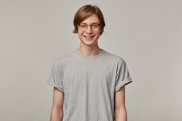 Portret van vrolijke, volwassen man met blond haar. het dragen van een grijs t-shirt, een bril en heeft beugels. mensen en emotie concept. glimlachend geïsoleerd over grijze muur