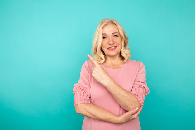 Portret van vrolijke volwassen vrouw die iets in de blauwe muur richt.