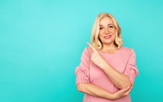 Portret van vrolijke volwassen vrouw die iets op de blauwe achtergrond richt.