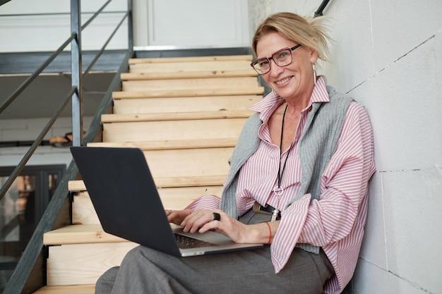 Portret van vrolijke volwassen zakenvrouw zittend op de trap en met behulp van laptop tijdens het opstellen van verkooprapport
