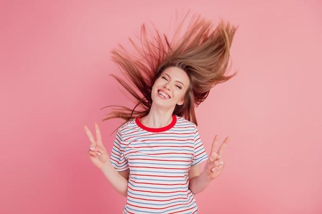 Portret van vrolijke vriendelijke dame toont v-tekens vredesgebaar op roze achtergrond
